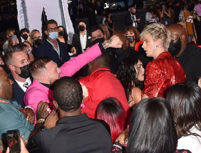 UGGEN STEMNING: Conor McGregor (t.v.) var ikke bare feststemt i møte med Machine Gun Kelly og Megan Fox. Foto: NTB