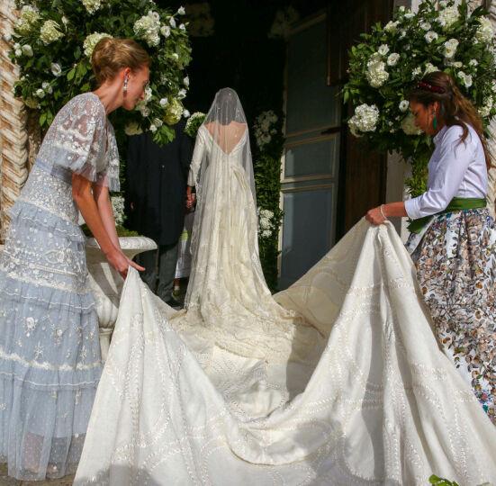FIKK HJELP: Den enorme kjolen krevde et par ekstra hender på vei inn i kirken. Foto: Frank Rollitz/Schneider-P/SIPA/Shutterstock/NTB